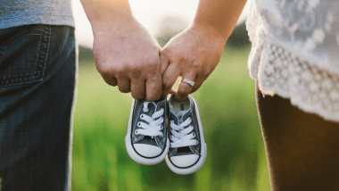 Married couple holding baby shoes